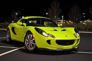 A green Lotus Elise at night.