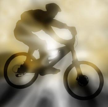 English: Silhouette of a mountain biker jumpin...