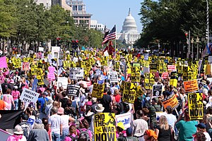 Protesters march down Pennsylvania Avenue towa...