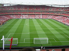 Pandangan interior sebuah stadion sepak bola. Tidak ada pemain di lapangan tetapi ada penonton di tribun.