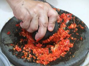 Chile peppers being ground into sambal