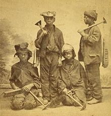 A studio portrait of four Afro-American climbing boys from New York, with brushes and scrapers, Two are standing and two are kneeling. They look between eleven and fourteen years old, wear rough clothes and battered hats and caps.