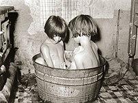 Bathing in a small metal bathtub