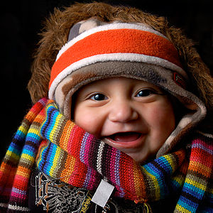 A baby wearing many items of winter clothing: ...