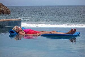 Mature lady sunbathing at swimming pool. Puert...