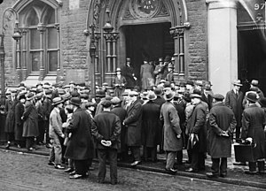 Unemployed men gather round the entrance to a ...