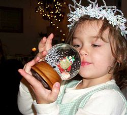 A girl shaking a snow globe.