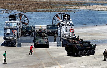 USMC LAV-25s and HMMWVs are offloaded from a U...