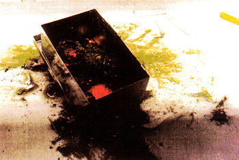 Glowing hot bits of plutonium in a box, which have been set alight due to plutonium's pyrophoric nature.
