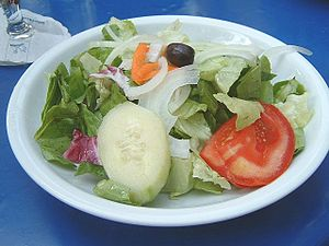 plate with green salad, onion, tomato, cucumbe...