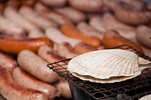 A scallop cooking on a grill. Sausages in the ...