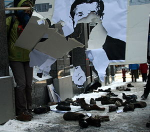 Montrealers throwing shoes at a poster of Geor...