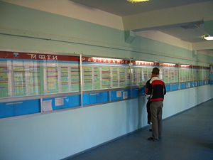 In front of the class schedule board on the 2n...