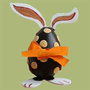 A chocolate egg decorated with bunny like ears...