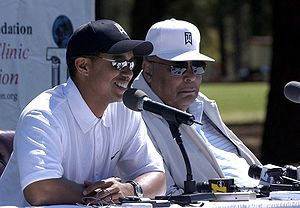 Golfer Tiger Woods, left, answers questions ab...