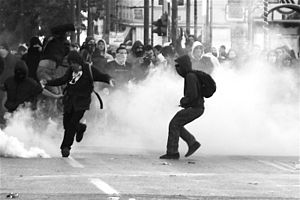 A rioter winds up to kick a smoke grenade back...