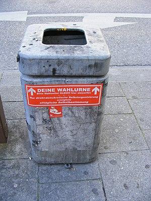 """Deutsch: Abfallbehälter mit Aufkleber """"De..."""