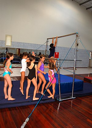 Girls lining up for practice on uneven bars