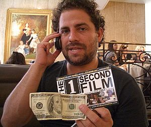 Brett Ratner holding a $100 bill and a produce...
