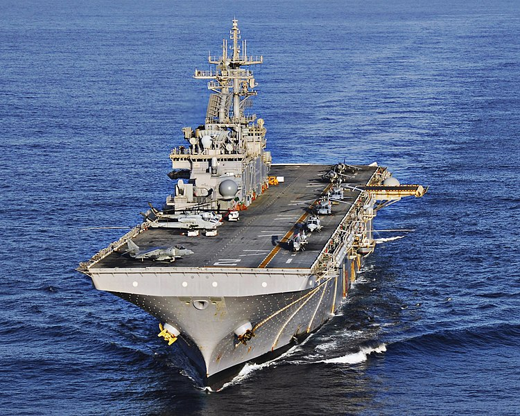 Picture of the USS Essex at sea, with helicopters and aircraft visible on its flight deck.