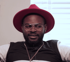 Falz wearing a red hat and a pair of round lens glasses