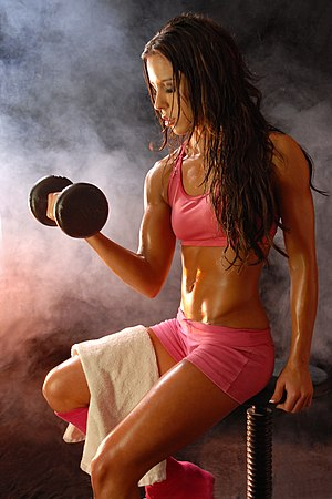 English: Fitness Model posing with dumbell. Ph...