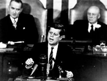 El presidente John F. Kennedy se dirige a una sesión conjunta del Congreso, con el Vicepresidente Lyndon B. Johnson y el Presidente de la Cámara Sam Rayburn sentado detrás de él.