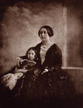 Victoria cuddling a child next to her