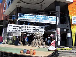 Building under renovation with banners in Spanish draping off the sides.