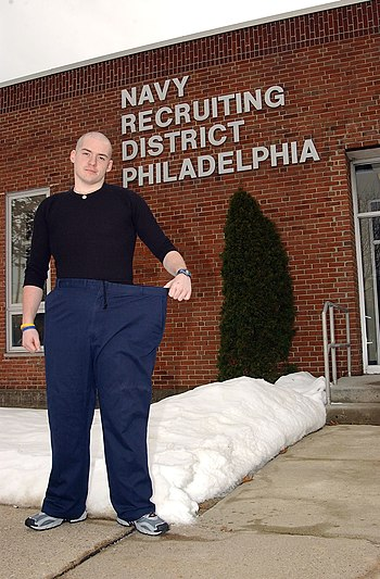 US Navy 050203-N-4729H-005 Navy Delayed Entry Program recruit Brian Connelly of Norwood, Pa., shows the pants he wore before he lost 175 lbs over the period of a year to join the U.S. Navy