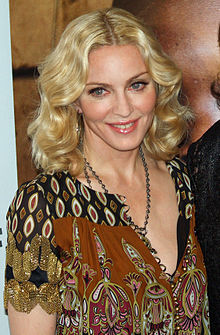 Upper body of a middle-aged blond woman. Her hair is parted in the middle and falls in waves to her shoulder. She is wearing a loose dress with black and brown prints on it. A locket is hung around her neck, coming up to her breasts. She is looking to the right and smiling.