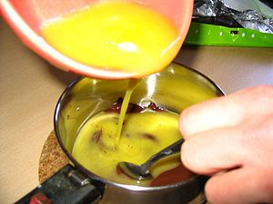 Mixing melted butter with chocolate to make a ...