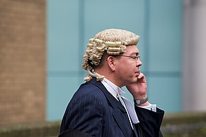 English: A barrister on a mobile phone outside...