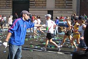 A volunteer hands out fluids at a marathon wat...