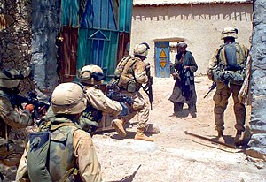 Foreign troops forcibly breaking into an Afgha...