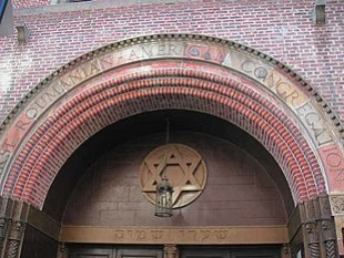 """The top of an arched reddish-brick entrance-way is visible. Carved into stones on the top row of the arch are the words """"First Roumanian-American Congregation"""", all in capital letters. The arch surmounts a brown wall with a bronze Star of David on it, with a lamp hanging from the arch in front of it. Underneath the brown wall, and above the doors, are inscribed the words """"Shaarey Shamoyim"""" in Hebrew."""