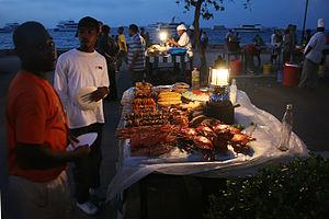 English: A food seller displaying his items at...