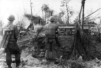 U.S. Marines move through the ruins of the ham...