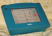 an electronic device about 20cm across, has a touchscreen showing communication symbols but no keyboard.