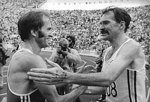 Gold medallist Robert de Castella (right) shak...