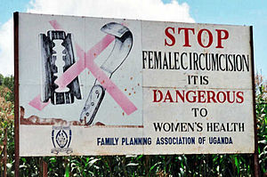 Billboard with surgical tools covered by a red X. Sign reads: STOP FEMALE CIRCUMCISION. IT IS DANGEROUS TO WOMEN'S HEALTH. FAMILY PLANNING ASSOCIATION OF UGANDA