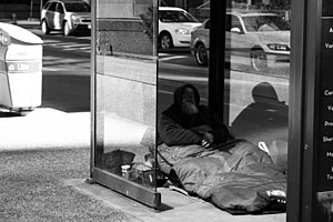 Homeless person in a bus shelter at York and W...