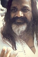 Closeup portrait of an Indian man with long black hair and mustache, and white beard