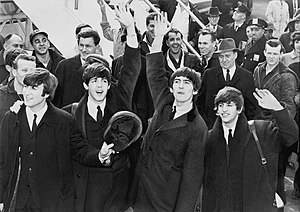 English: The Beatles wave to fans after arrivi...