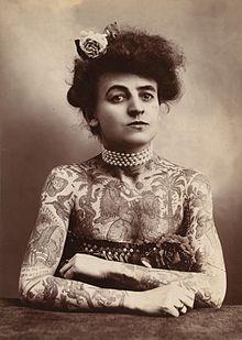storia del tatuaggio - Donna tatuata fotografata nel 1907 - Violet Fire Tattoo & Piercing - Adam Raia - violet fire tattoo, tatuaggi maranello, tatuaggi modena, tatuaggi sassuolo, tatuaggi fiorano, tatuaggio nichel free, tatuaggio senza nichel, tatuaggio vegano, nickel free tattoo, vegan tattoo, tatuaggio vegan ok, italian tattoo, tatto italy, tattoo maranello, tattoo modena, tatuaggi emilia tattoo, tatuaggi emilia romagna tattoo, tatuaggio emilia romagna, tricopigmentazione maranello, micropigmentazione maranello, tricopigmentazione modena, micropigmentazione modena - piercing nichel free, piercing senza nichel, nickel free piercing, italian piercing, piercing italy, piercing emilia, piercing emilia romagna piercing - piercing maranello, piercing modena, piercing sassuolo, piercing fiorano, piercing formigine, piercing casalgrande, piercing castellarano, piercing scandiano, piercing castelnuovo, storia del tatuaggio, storia tatuaggio, tatuaggio storico, storia del piercing, piercing storico