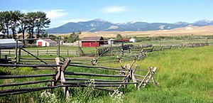 Photograph of a split-rail fence and ranch bui...