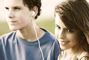 Teens sharing earphones, listening music outdo...