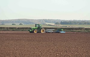 English: The Farmer is busy Ploughing and till...