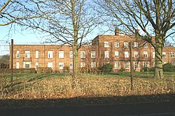 A tall wire fence separates the viewer from a long red brick multi-storey building, set in parkland.