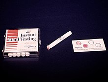 A box of cigarette-like white cylinders on the left, in the middle a white cylinder with a pink tip, on the right a paper with four circles, two blank and two pink